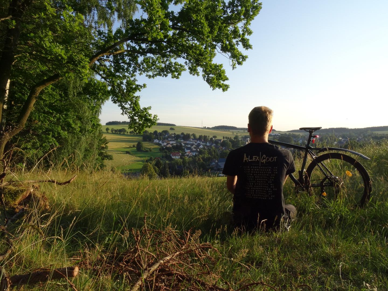 Ich von Hinten, sitzend auf einer Wiese in einem Landschaftsbild.