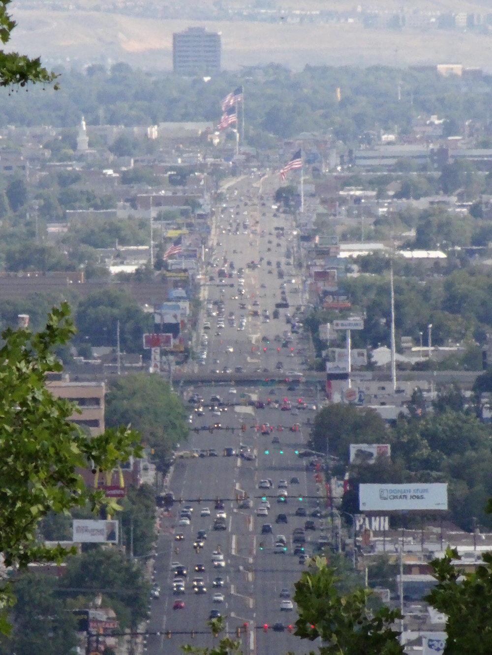 Blick mit optischer Vergrößerung auf eine große Straße Salt Lake Citys vom Parlament aus.